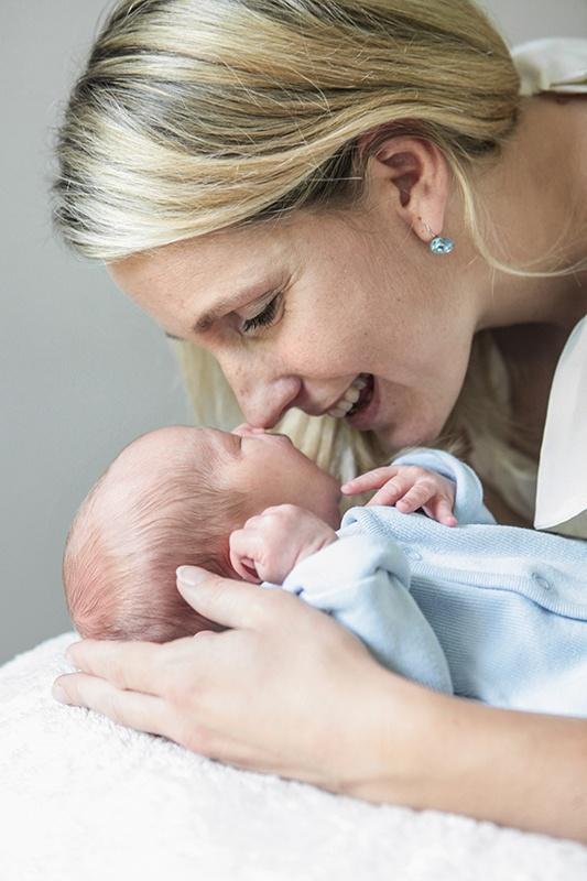 Eine Mutter blickt auf das Baby herunter, dass es in den Händen ganz nah vor ihr Gesicht hält. Ihre Nasen reiben scheinbar aneinander. Das Neugeborene streckt den Kopf ein bischen in Richtung Mama. Die lächelt ihr Kind an.