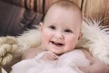 Ein nacktes Baby in einem Korb, umgeben von Tauen, Fell, Gardinenstoff.  Im Hintergrund: eine Holzwand. Das Kleinkind strahlt.