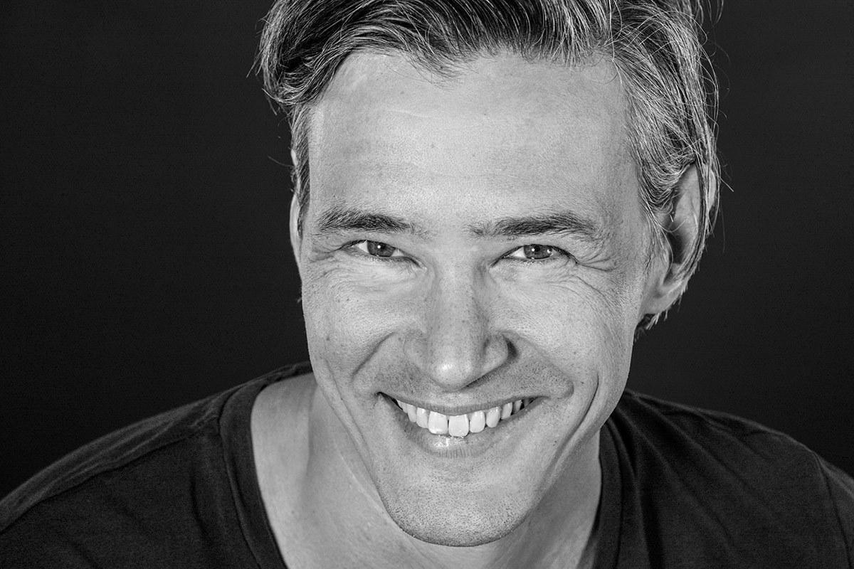 Das Foto ist schwarzweiß: Ein Mann in einem dunklen Shirt lächelt selbstbewußt in die Kamera des Fotografen Franz Fender aus Hannover. Der Bewerber hebt sich trotz  dunklem Shirt durch die geschickte Lichtführung vom schwarzen Hintergrund ab.