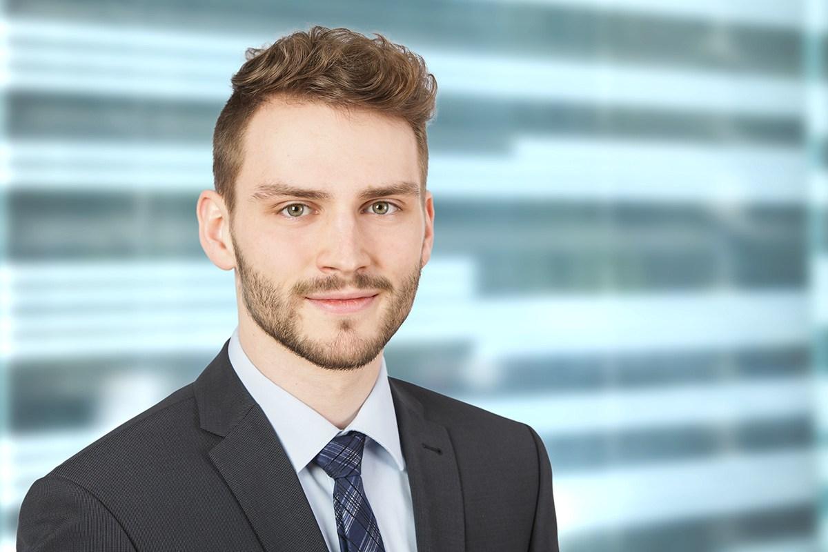 Ein junger Mann steht vor einer hellen türkisfarbenen Gebäudefront. Er dreht sich leicht nach rechts und blickt gelassen in die Kamera.