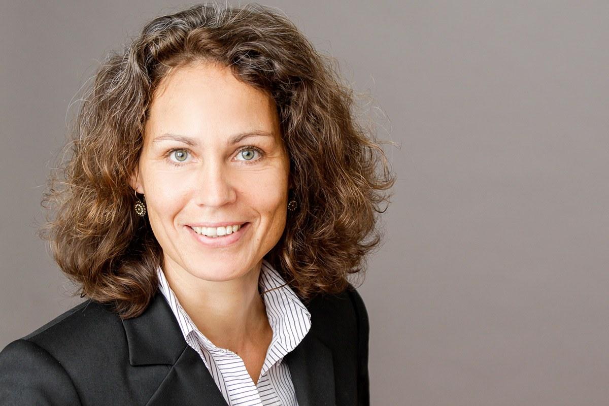 Eine junge Frau sitzt seitlich nach rechts gedreht mit Blick zur Kamera vor einem grauen Hintergrund: das typische Bild für das Deckblatt einer Bewerbungsmappe.