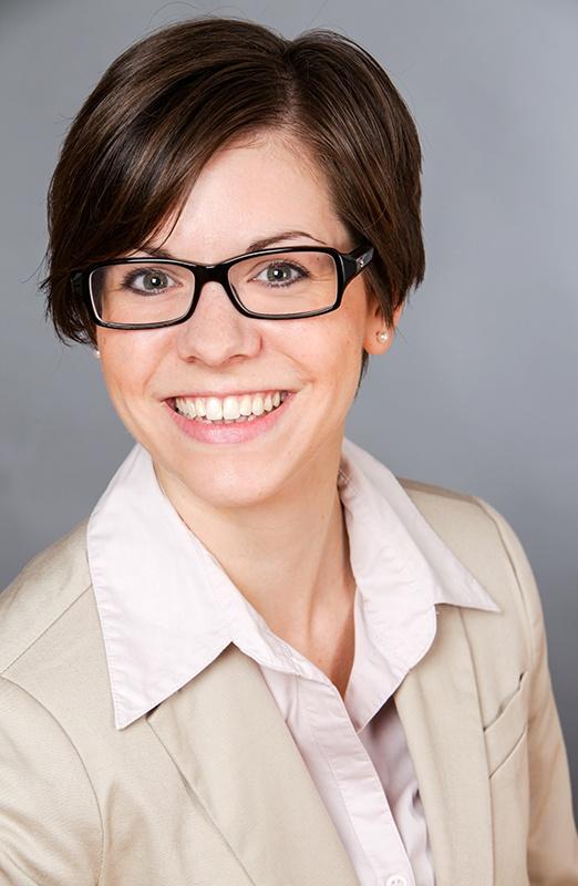 Ein hochformatiges Bild: eine junge Frau im beigen Blazer, heller Bluse,  mit Brille  sitzt nach rechts gedreht und lächelt in die Kamera. Diese Bildgestaltung (Hochformat, nach rechts gedreht) buetet sich bei Bildern für den Lebenslauf an, die auf der linken Seite des CV stehen.