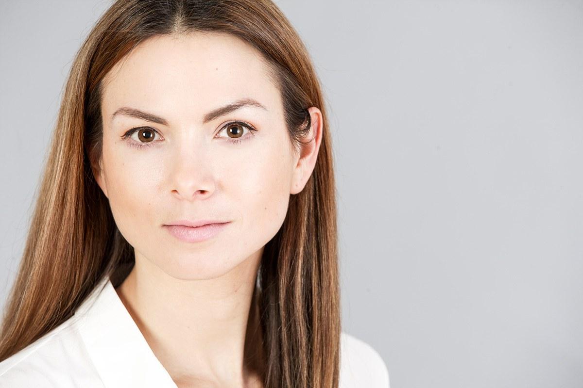 Eine Frau Anfang dreißig mit langen gepflegten braunen Haaren, braunen Augen, weißer Bluse sitzt im Oberkörper nach rechts gedreht und guckt guckt ernst aber durchaus sympathisch in die Fotokamera des Bewerbungsfotografen.