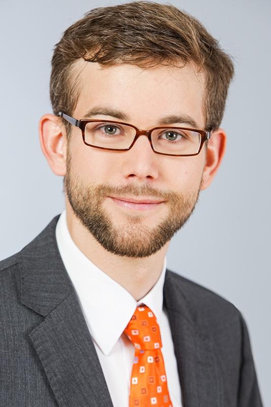 Am auffälligsten an diesem Bewerbungsfoto ist die orangene Krawatte. Der Bewerber hat sich ansonsten für ein klassisches Outfit bestehend aus grauem Sakko und weißem Hemd entschieden.  Passend dazu: der graue Hintergrund. Allein Krawatte und eine  hellbraune Hornbrille sorgen für Pepp im Bild.