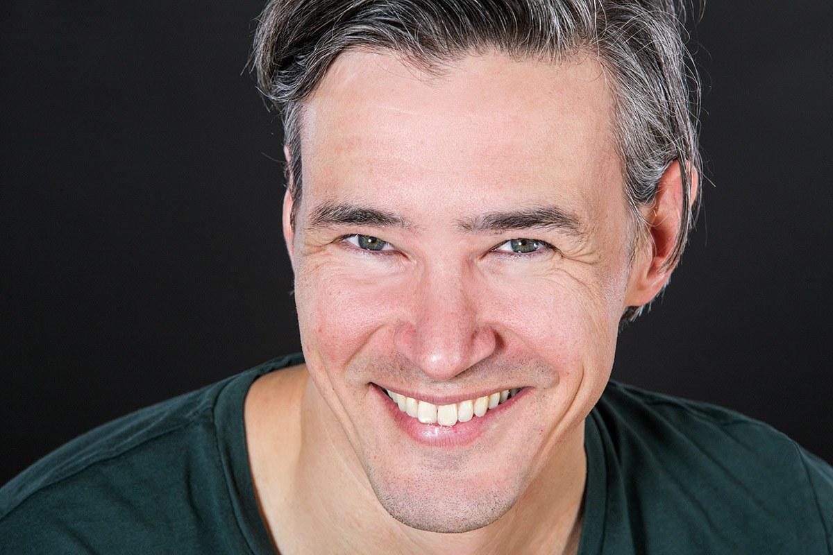 Ein Mann in einem grünen Shirt lächelt selbstbewußt in die Kamera des Fotografen Franz Fender aus Hannover. Der Bewerber, der sich für eine Stelle in einem kreativen Beruf bewirbt, hebt sich durch geschickte Lichtführung vom schwarzen Hintergrund ab.