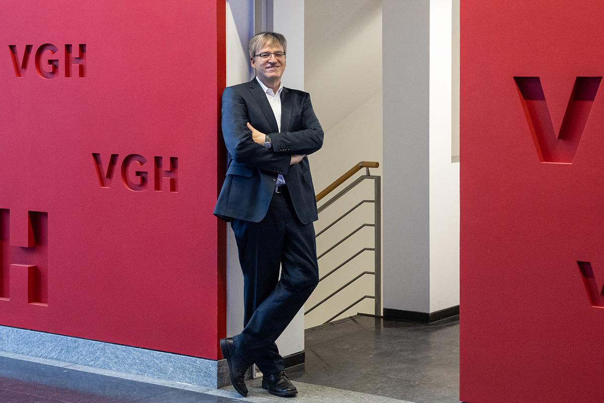 Volker Pätzold, Bereichsleiter  Asset Management der VGH Versicherungsgruppe Hannover, lehnt entspannt  lächelnd an einem Türrahmen im Foyer  des Unternehmensgebäudes.