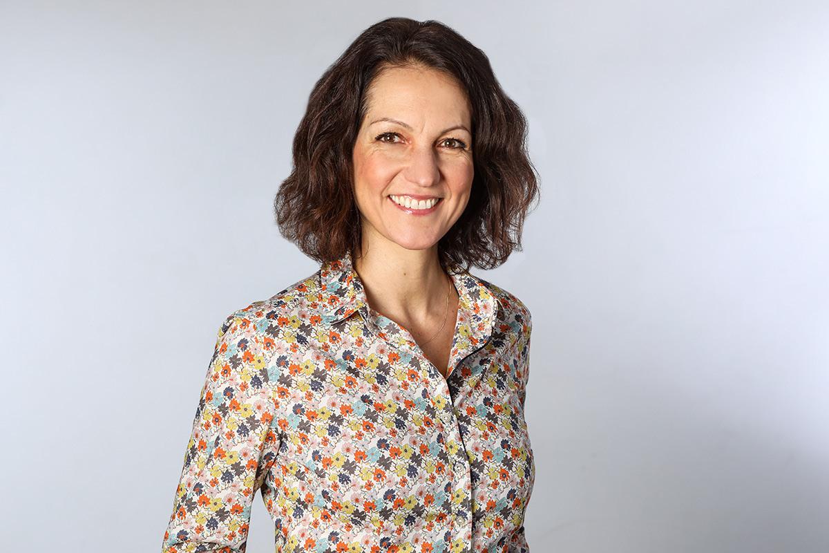 Die Heilpraktikerin Britta Struckmann ist im Oberkörper zu sehen. Sie trägt eine bunte Bluse und steht vor einem grauen Hintergrund. Ihr Lächeln  ist einnehmend.