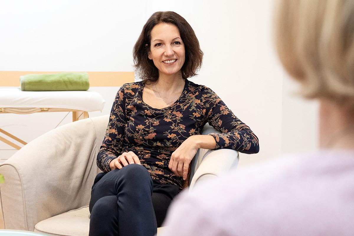 Die Patientin sitzt mit dem Rücken zur Kamera. Lächelnd sitzt ihr gegenüber die Therapeutin, die ihrer Patientin gerade interessiert zuzuhören scheint.