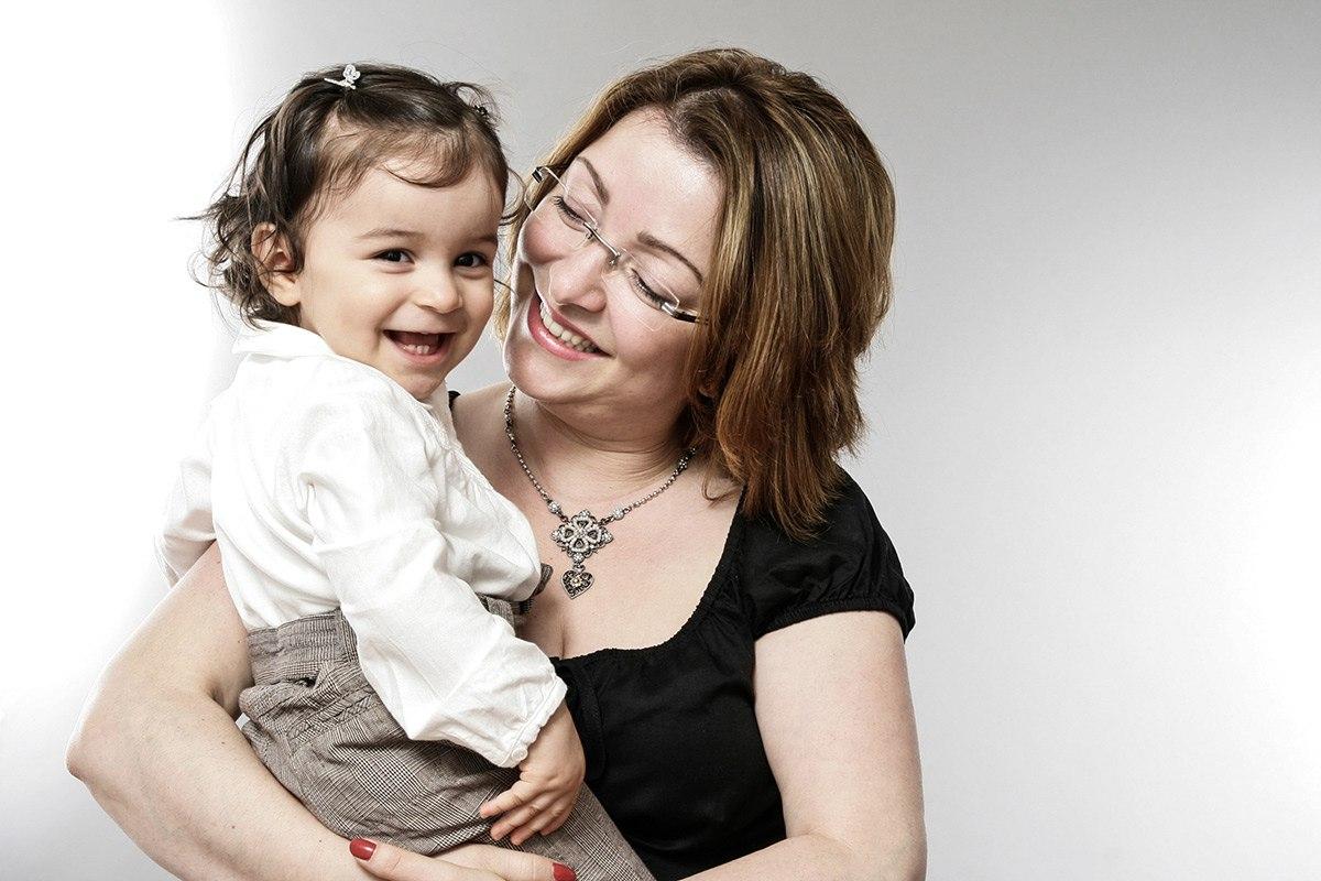 Eine Mutter im schwarzen Oberteil hält ihr Kind auf dem Arm. Das Kind trägt eine weiße Bluse. Der Hintergrund des Bildes ist hellgrau. Die Mutter blickt mit sanftem Blick zu ihrer Tochter, das Kind strahlt in die Kamera.