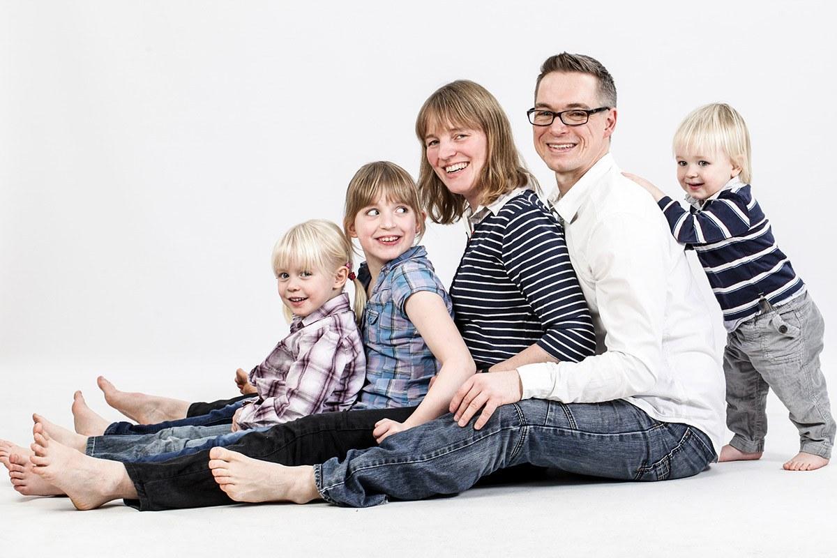 Eine fünfköpfige Familie sitzt seitlich auf dem Boden. Sie sitzen hintereinander mit gespreizten Beinen, der Vater ganz rechts, immer das nächst kleinere Familienmitglied vor ihnen.  Nur der kleinste Sproß, etwa eineinhalb Jahre alt, steht hinter seinem Vater und lehnt sich mit einem Arm an Papas Rücken an.