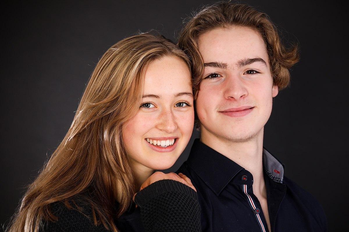Eine etwa 18jährige junge Frau hat ihre Hand auf die Schulter ihres Bruder gelegt. Der steht mit dem Rücken zu ihr, ihre Köpfe berühren sich leicht. Die Geschwister sind sehr hübsch. Beide lächeln glücklich in die Kamera.