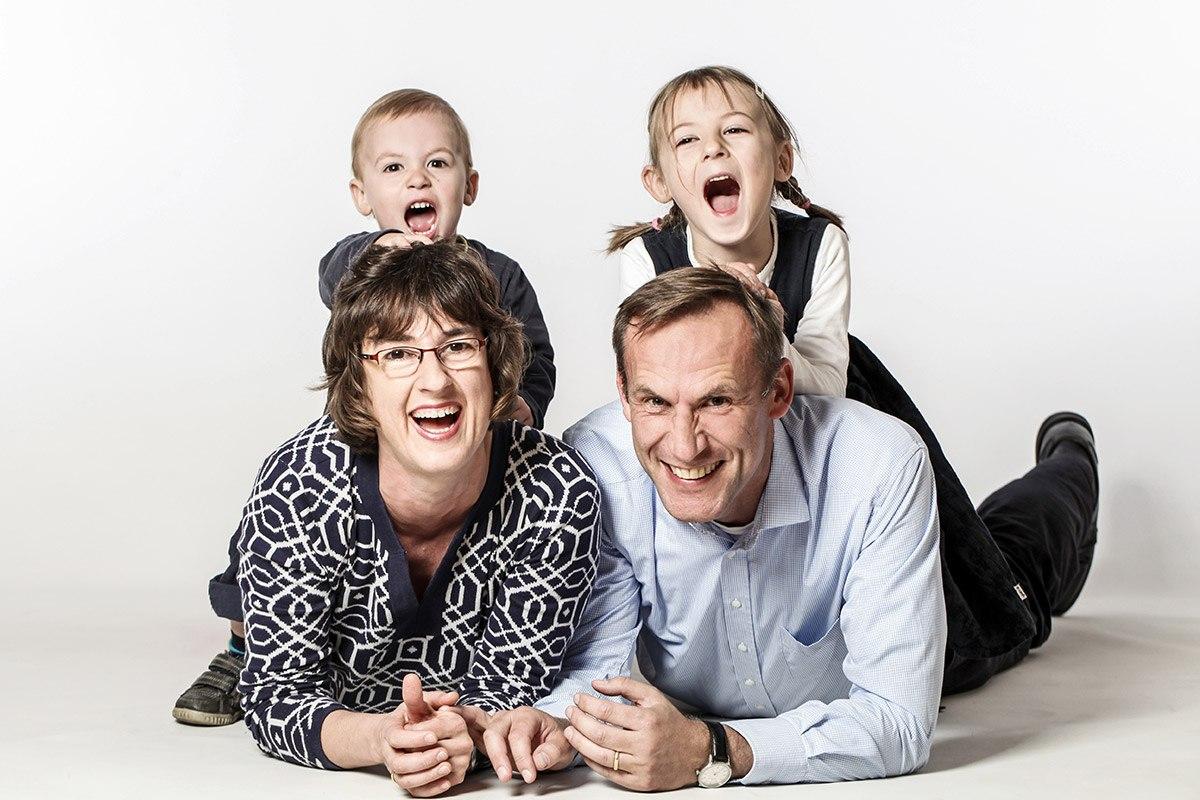 Vater und Mutter liegen bäuchlings auf dem Boden und stützen sich mit den Ellbogen ab. Ihre etwa 4 und 7 Jahre alten Kinder hocken auf ihrem Rücken und halten sich an den Haaren der Eltern fest. Die Münder der Kinder sind sperrangelweit auf vor Begeisterung, die Eltern lachen ausgelassen.