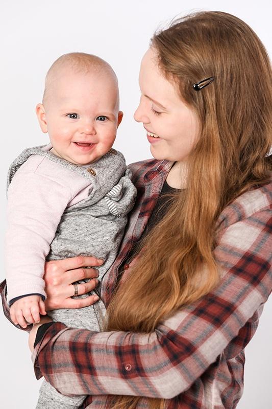 Ein älteres Mädchen hält sein mehrere Monate altes Geschwisterchen auf dem Arm. Das Baby strahlt Richtung Kamera, die Schwester lächelt das Baby an.