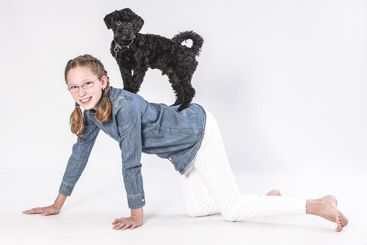Ein knapp 10 Jahre altes Mädchen steht seitlich auf allen Vieren. Ihr Blick geht zur Kamera. Auf ihrem Rücken balanciert ein schwarzer Pudel, der gleichfalls in die Kamera guckt. Der Blick des Hundes ist sehr ernst, das Mädchen lacht.
