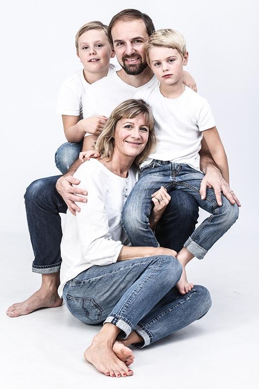 In  der Mitte des Bildes sitzt der Vater auf einem Hocker. Auf seinem linken Bein sitzt sein Sohn. Sein älterer Sohn sitzt hinter ihm und guckt ihm über die Schulter.  Vor ihm hockt seine Frau, seine rechte Hand umarmt sie. Alle tragen weiße T-Shirts und blaue Jeans und lächeln in die Kamera.