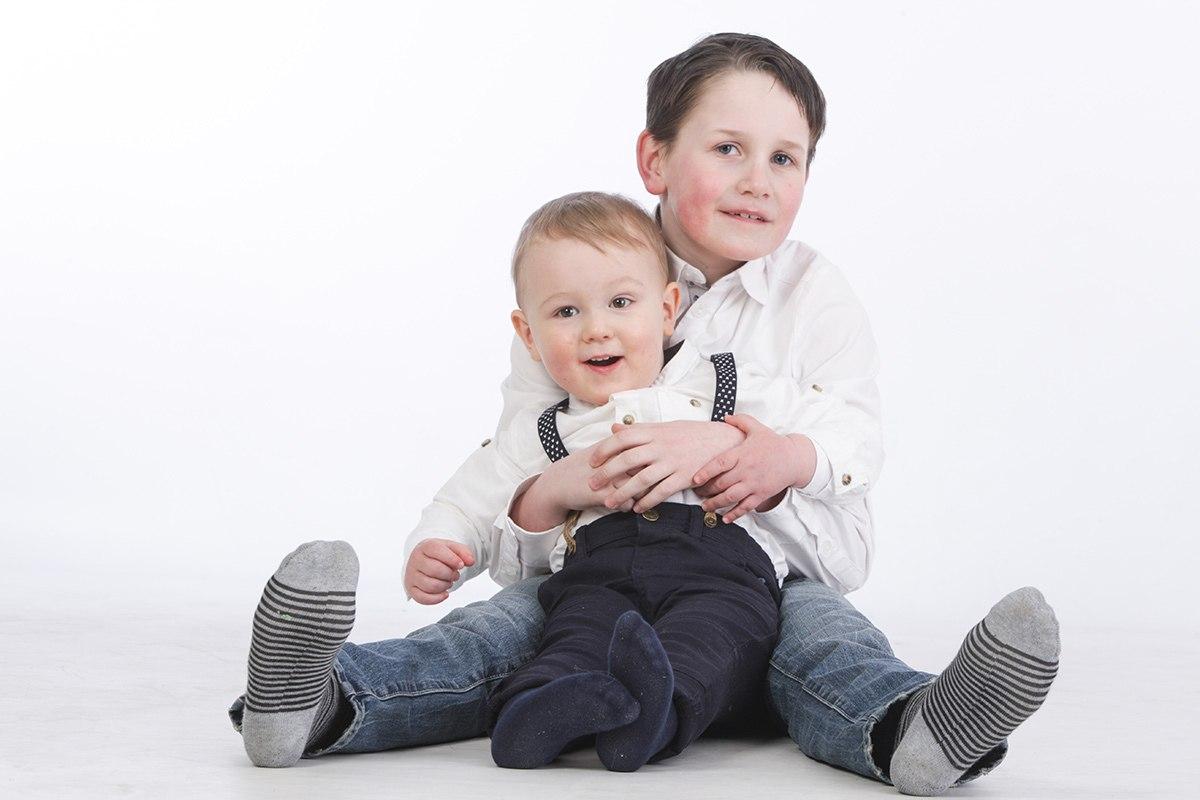 Ein Junge sitzt auf dem Boden frontal zur Kamera. Zwischen seinen gespreizten Beinen sitzt sein jüngerer Bruder, den er von hinten mit beiden Händen umfasst. Beide Jungs haben weiße Hemden an. Der Hintergrund des Bildes ist weiß.