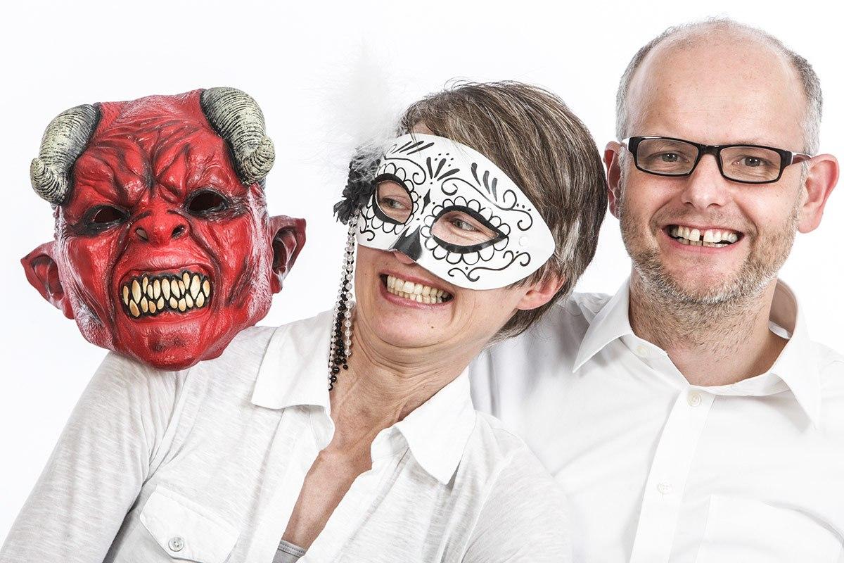 Rechts im Bild ist ein Mann, seine links von ihm sitzende Frau trägt eine venezianische Maske. Sie dreht sich von der Teufelsfratze auf ihrer Schulter weg und presst sich an ihren Mann.  Obwohl sie zurückweicht, lacht sie. Ihr Mann lacht, dem Bildbetrachter zugewandt.