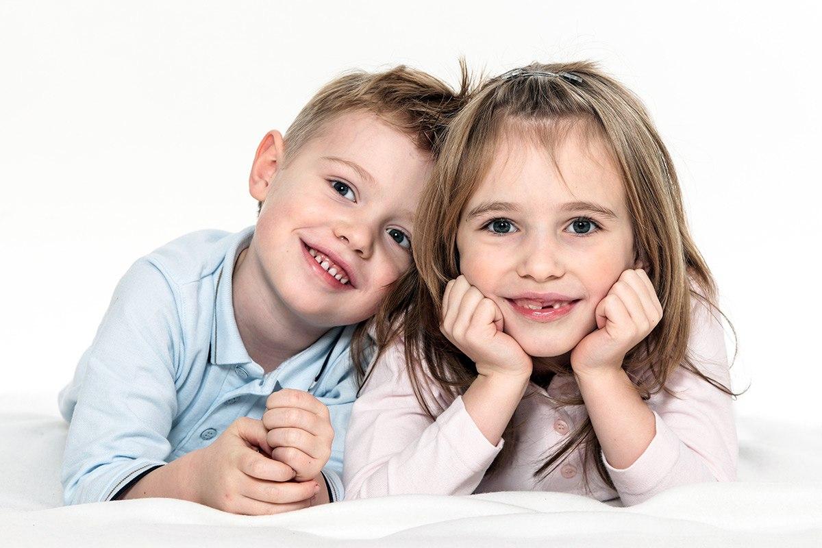 Das Mädchen liegt bäuchlings auf dem Boden und hat das Gesicht auf die angewinkelten Arme gestützt. Ihr Bruder liegt neben ihr und lehnt seinen Kopf an ihre Schulter. Beide lächeln, wodurch ihre Zahnlücke bei den oberen Schneidezähnen sichtbar wird.