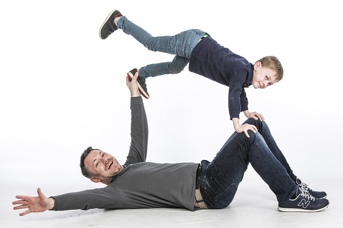 Der Vater liegt rücklings auf dem Boden, Beine angewinkelt, die Arme wie nach einem Turnelement von sich gestreckt. Sein Sohn hält sich mit den Händen an Vaters Knien fest , der linke Fuß steckt in dessen Hand und der rechte Fuß holt scheinbar aus zum Schwung  für den Kopfstand.