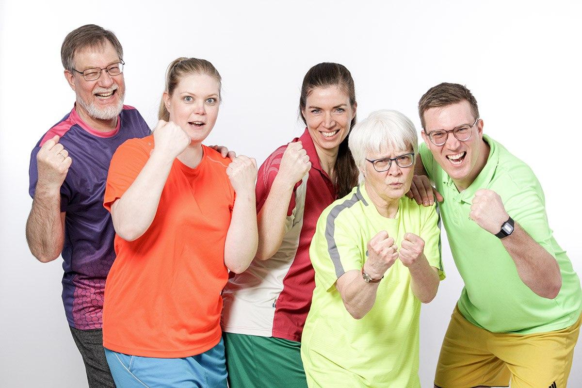 Eine fünfköpfige Familie steht unsortiert mit Blick zur Kamera. Die Fäuste sind wie zum Boxkampf erhoben. Sie tragen verschiedenfarbige Sportoberteile und Sporthosen.