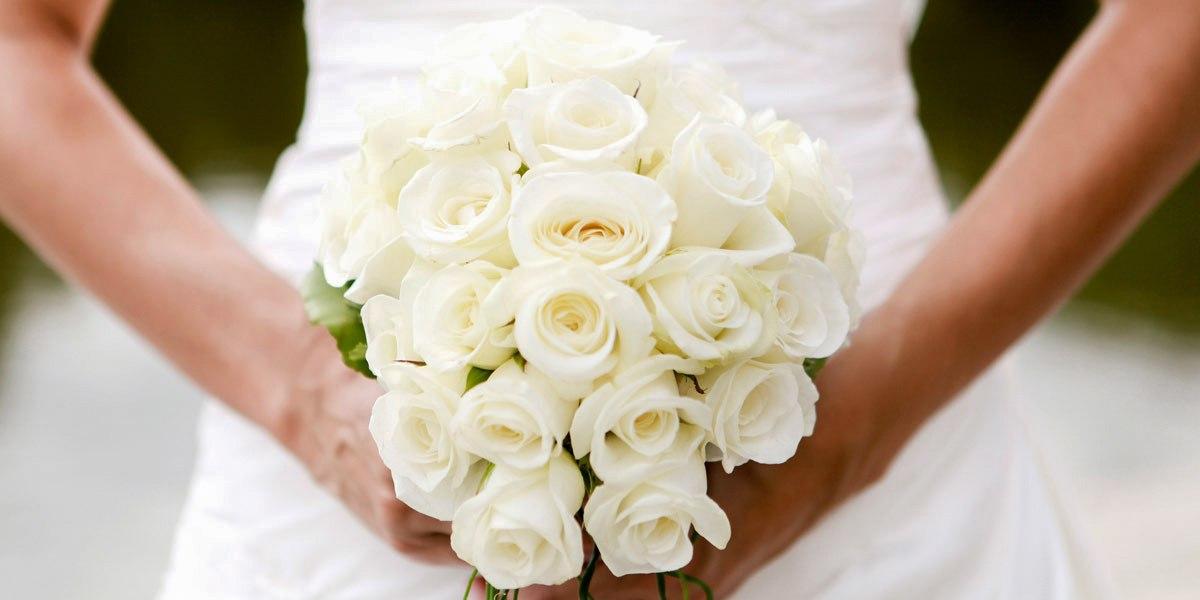 Viele weiße Rosen füllen das Bild zur Hälfte aus. Den Strauß hält eine Braut, deren Unterarme von links und rechts ins Bild kommen, weil sie den Brautstrauß etwa in der Höhe ihres Bauchnabels hält. Sie trägt ein weißes Kleid.