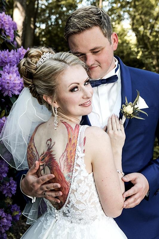 Das tief ausgeschnittene Brautkleid gibt den Blick frei auf das schöne Tattoo: ein großer Greifvogel auf dem Rücken der Braut.  Sie schmiegt sich an an ihren Mann und guckt über ihre Schulter in die Kamera des Fotografen Franz Fender. Der Bräutigam trägt einen dunkelblauen Anzug, eine passende Fliege und ein weißes Hemd.