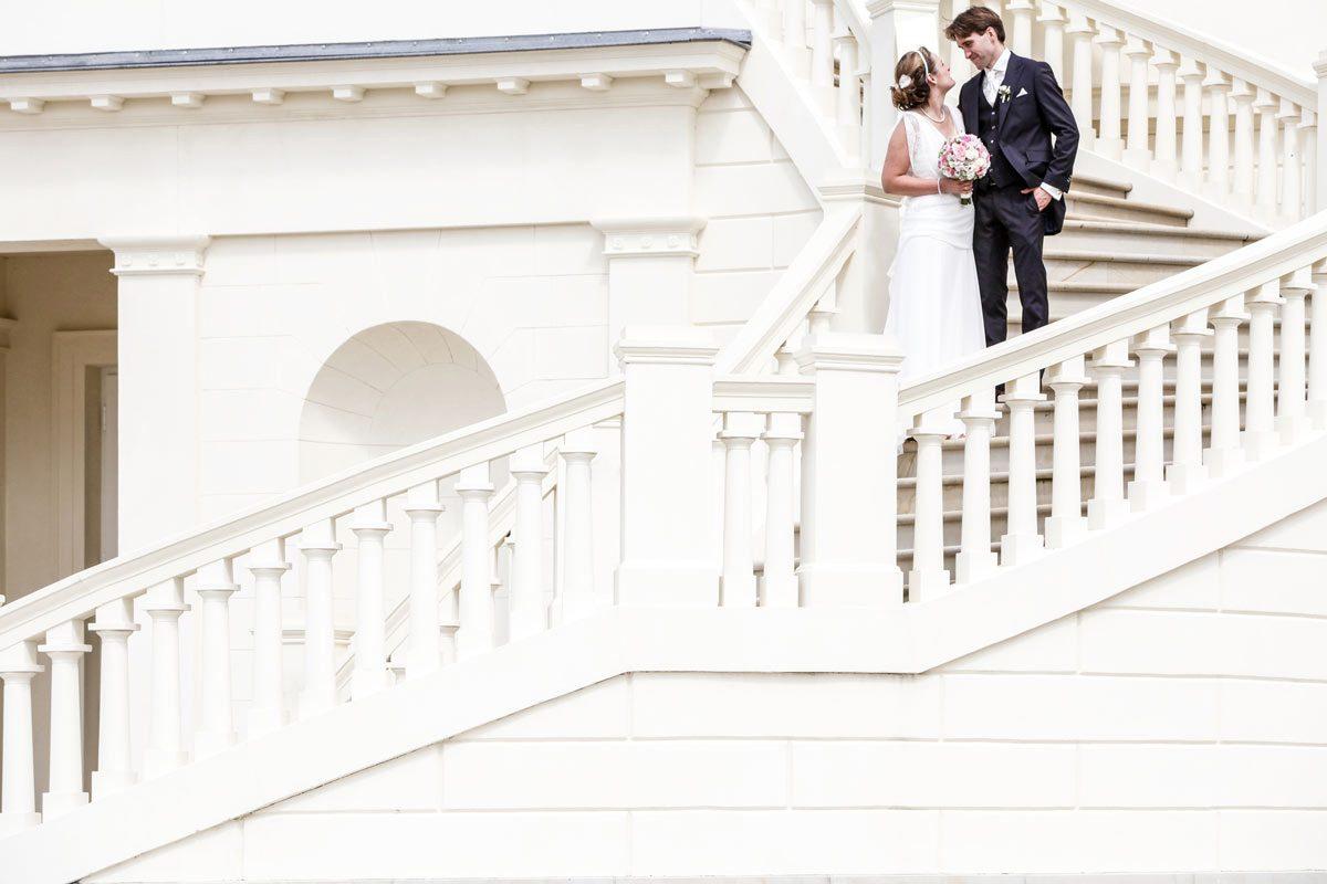 Ein Brautpaar steht auf den Treppenstufen des Schloss Herrenhausen in Hannover. Der Bräutigam im dunkelblauen Anzug hat die Finger seiner linken Hand locker in die Hosentasche geschoben und guckt auf seine Frau. Die Braut im langen weißen Kleid steht mit dem Brautstrauß in der Hand eine Stufe unter ihm auf der geschwungenen Schlosstreppe. Gesehen und fotografiert hat das frisch vermählte Paar Hochzeitsfotograf Franz Fender aus Hannover.