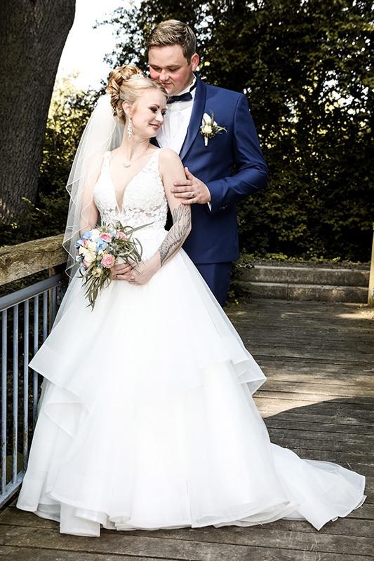 Ein Brautpaar hat sich die Holzbrücke im Garten des Wilhelm-Busch-Museums Hannover als Location für ein Foto-Shooting ausgesucht. Sie trägt ein weißes Brautkleid mit viel Spitze, Tüll und Schleier. Sein Anzug ist blau mit passender Fliege und weißer Ansteckblume. Er steht hinter ihr und hält sie. Sie genießt.