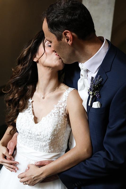 Die Braut trägt ein weißes verspieltes Brautkleid, sein Outfit ist ein dunkelblauer Anzug mit weißer Krawatte. Sie ist mit dem Rücken an seine Brust gedrückt. Er steht hinter ihr. Sie dreht ihren Kopf zu ihm über ihre Schulter. Beide küssen sich leidenschaftlich.