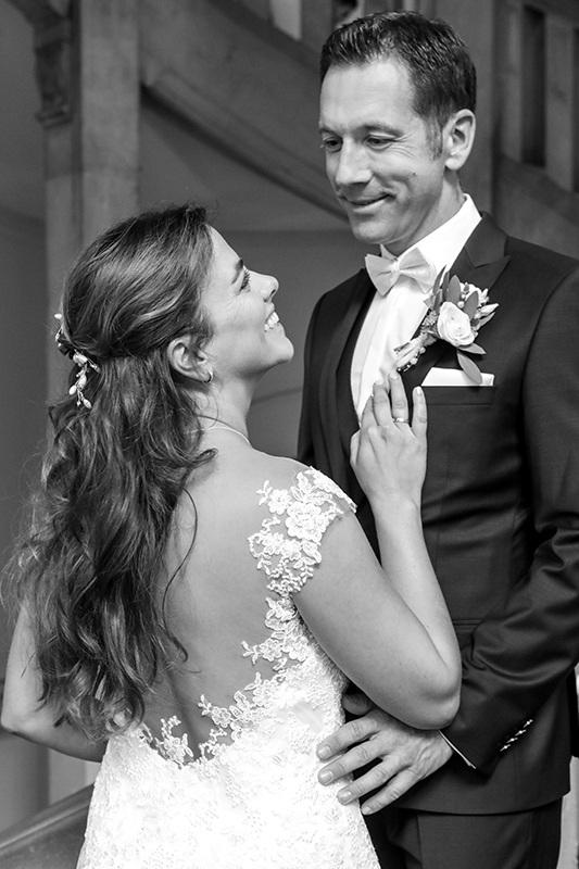 Sie steht leicht mit dem Rücken zur Kamera. Das lange braune Haar bedeckt ihren Rücken, den das spitzenreiche Brautkleid ausspart. Ihre Hand liegt auf seiner Brust, während sie ihn mit offenem Mund anstrahlt. Der Bräutigam steht etwas über ihr auf der Treppe im Neuen Rathaus Hannover und erwidert ihren strahlenden Blick.  Das Bild ist schwarzweiß.