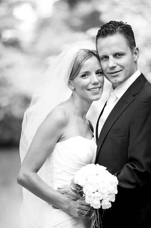 Passend zum Motiv dominiert ganz weiches Licht das schwarzweiße Bild. Braut und Bräutigam sind sehr schlank und haben fein geschnittene Gesichter. Sie tragen eher sportliche Outfits, ohne Schnickschnack, und stehen seitlich zur Kamera, lehnen ihre Wangen aneinander und lächeln. Die hellen Blätter der Bäume hinter dem Brautpaar sorgen durch eine extreme Unschärfe für  einen hell flimmernden Hintergrund.