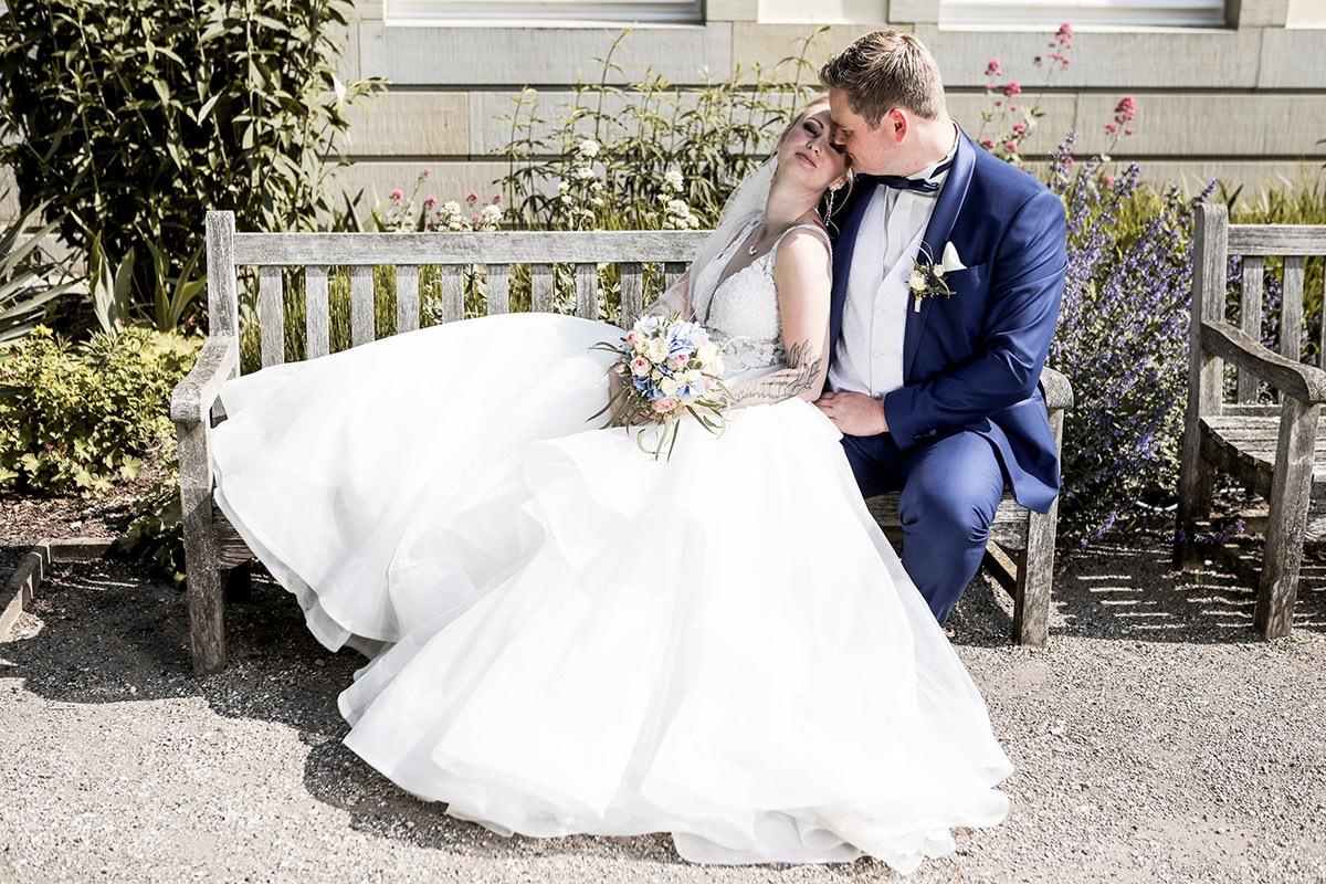 Der Bräutigam sitzt aufrecht auf der rechten Seite der Gartenbank. Seine Frau lehnt sich mit geschlossenen Augen an seiner Schulter an. Sie genießt die Sonne und seine Nähe. Ihr fülliges Kleid reicht von der anderen  Armlehne der Bank bis zum Knie des Bräutigams und bedeckt komplett den Kiesboden vor der Bank. Der Bräutigam betracht das Gesicht seiner Frau, das wenige Zentimeter vor ihm an seiner Brust lehnt.