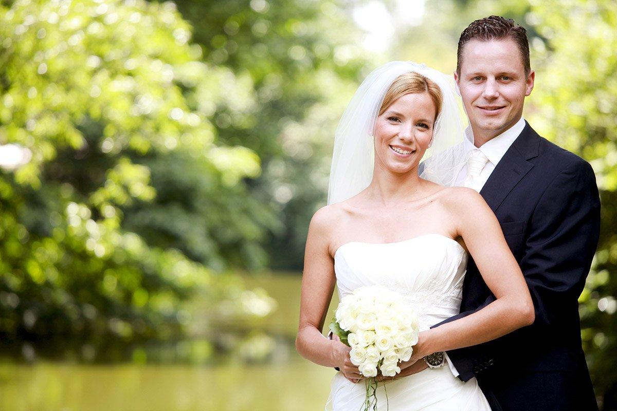 Das Brautpaar und der Hintergrund des Bildes sind durch eine extreme Schärfe/Unschärfe voneinander getrennt. Braut und Bräutigam befinden sich zudem nur im rechten Teil des Bildes. Sie steht im weißen Kleid mit dem Brautstrauß in der Hand vor ihm.  Sein Outfit besteht aus dunklem Anzug mit weißer Krawatte. Beide gucken gutgelaunt geradeaus.