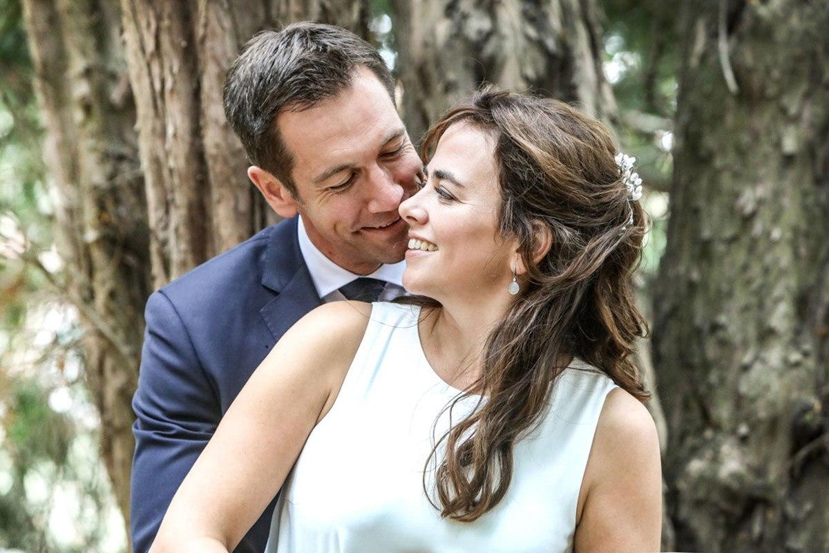 Das Brautpaar steht vor einem knorrigen alten Baum im Park des Standesamtes in Laatzen. Sie dreht ihr Gesicht über ihre rechte Schulter zu ihrem hinter ihr stehenden Mann. Sie trägt ein  schlichtes weißes Kleid, er hat einen blauen Anzug mit Krawatte gewählt. Sie lächeln sich an.