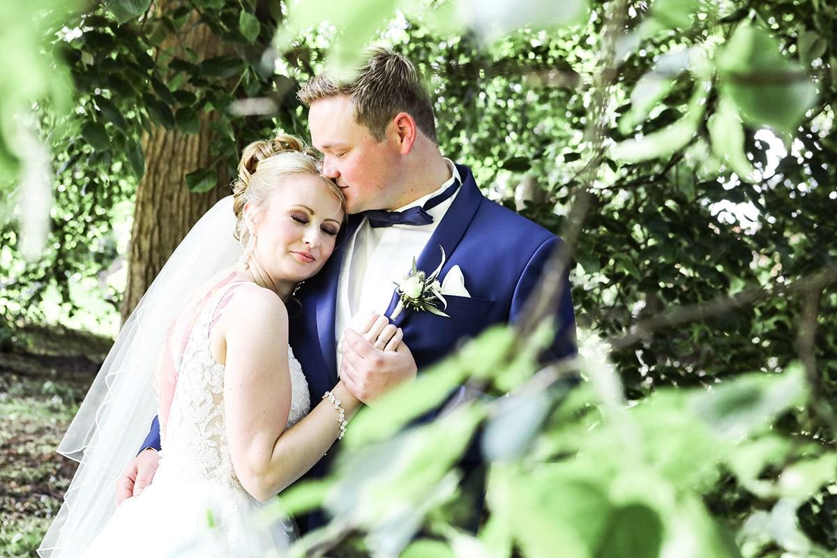 Der Blick geht durch dichtes Blattwerk hindurch. Braut und Bräutigam haben die Augen geschlossen und genießen. Sie im weißen Kleid mit Schleier lehnt an ihm und hat ihren Kopf an seine rechte Schulter gedrückt.  Er hält ihre Hand und schmiegt Mund und Nase an ihr Haar.  |