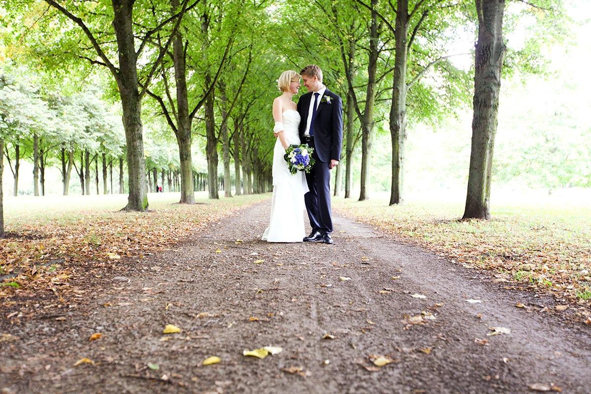 Das Brautpaarfoto ist leicht von unten aufgenommen. Mann und Frau stehen vor einer langen Baumallee, die im Hintergrund verschwimmt. Von vorn führt ein brauner herunter getretener Weg auf das Brautpaar zu. Das erste Herbstlaub liegt am Boden. Das Brautpaar hat sich einander zugewandt und sie blicken sich tief in die Augen.