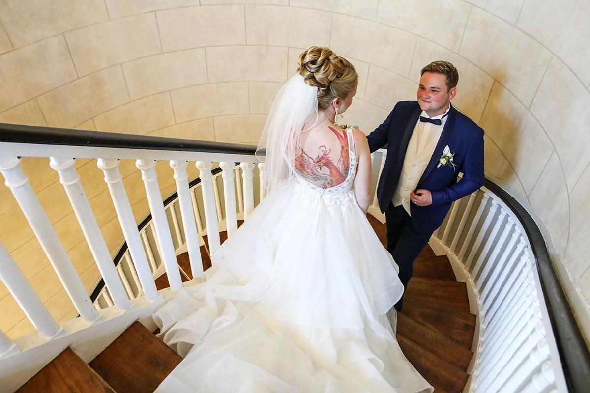 Eine Braut mit einem weißen Brautkleid, langer Schleppe und einem Schleier im Haar geht im Wilhelm-Busch-Museum Hannover die Treppe herunter. Im Ausschnitt ihres rückenfreien Kleides sieht man einen großen tätowierten Greifvogel. Ihr Bräutigam im blauen Anzug mit blauer Fliege kommt ihr treppauf entgegen.