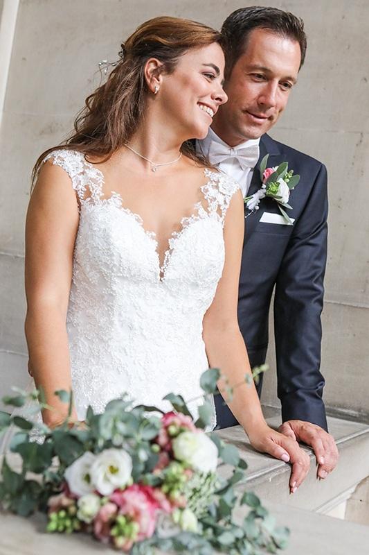 Der Brautstrauß im Bildvordergrund liegt auf der Brüstung der Balustrade und ist unscharf. Scharf ist das dagegen das Brautpaar knapp dahinter, das vor einer Steinmauer steht, auf irgendetwas hinunter blickt und sich freudestrahlend unterhält. Der schönste Tag im Leben.