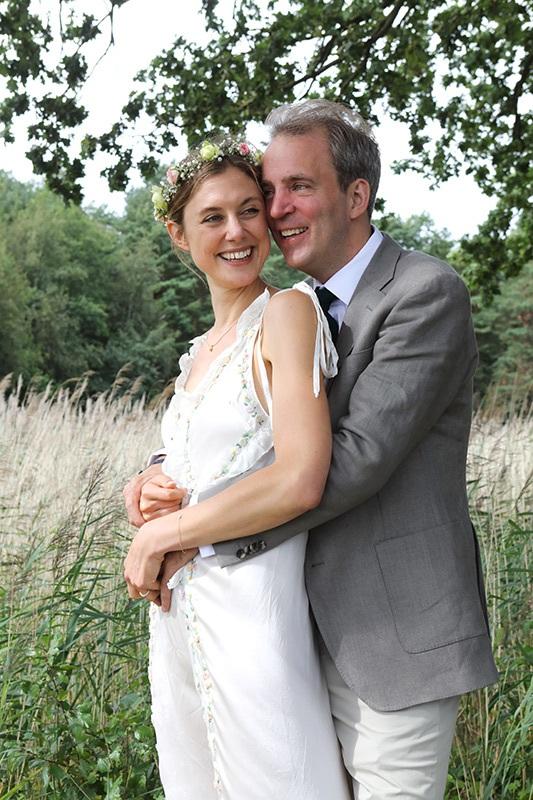 Die Braut trägt eine Hochzeitskrone aus geflochtenen Blumen, ihr Kleid  wirkt wie ein luftiges weißes Sommerkleid.  Ihr Bräutigam steht hinter ihr und hält sie im Arm. Sie dreht ihr lachendes Gesicht über ihre linke Schulter zu ihm.  Er schmiegt seinen Kopf an ihre Wange. Schilf biegt sich leicht hinter dem Brautpaar im Wind.  Dahinter: der Waldrand.