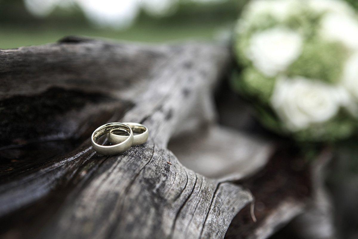 Trauringe drapiert auf einem Baumstamm, im Hintergrund der Brautstrauß. Die Schärfe im Bild liegt nur auf den Brautringen und auf dem kleinen Stück des Stammes, auf dem die Ringe liegen.