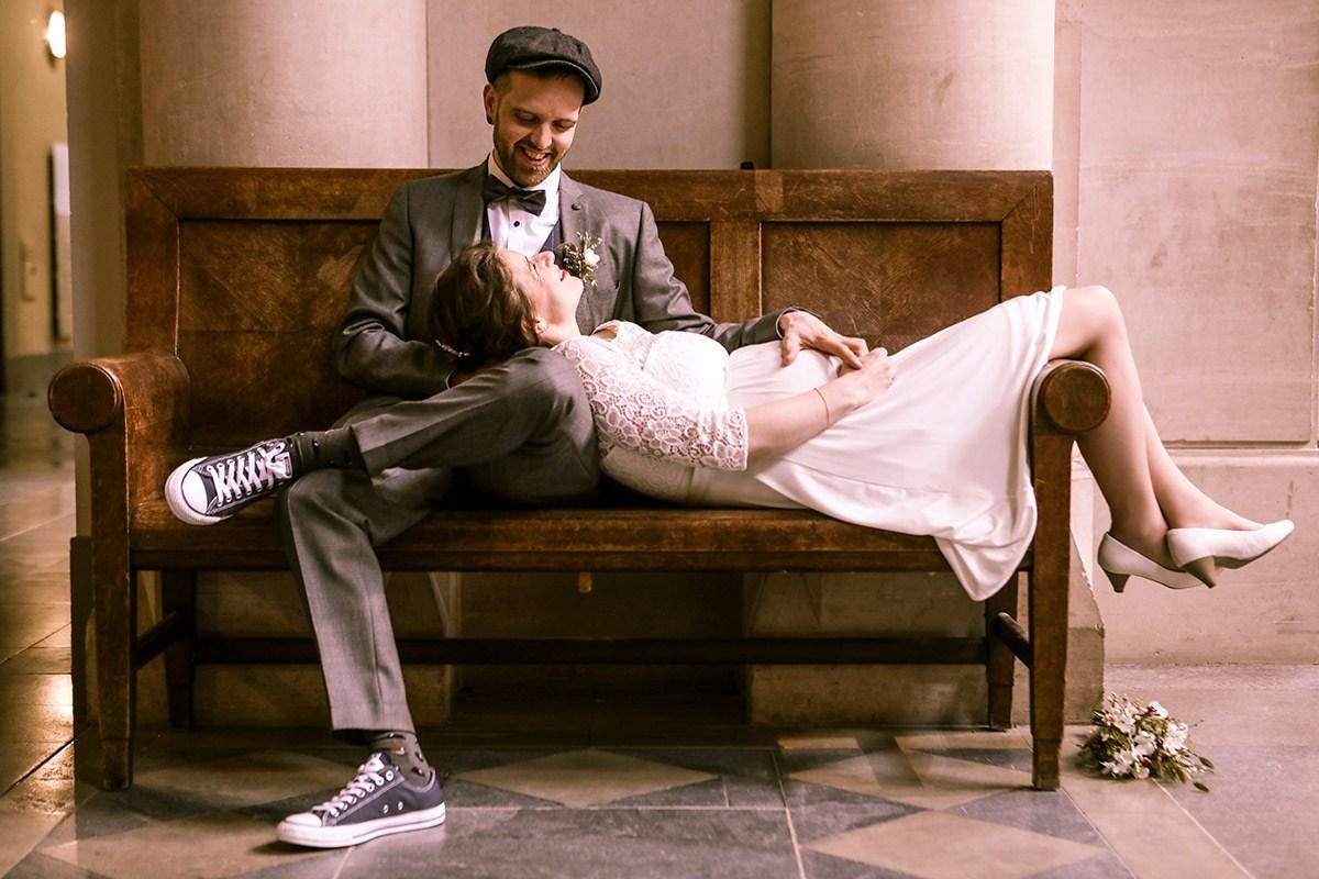 Die Braut guckt verträumt zum frisch vermählten Mann: ihre Beine läßt sie über die Banklehne baumeln, ihr Kopf liegt auf seinem Oberschenkel, während ihre Hände sich schützend über ihren Babybauch legen. Sie trägt ein weißes Brautkleid. Er trägt einen karierten Anzug mit Schiebermütze, Turnschuhen. Er sitzt normal auf der Bank im Neuen Rathaus Hannover. Er lächelt zurück.