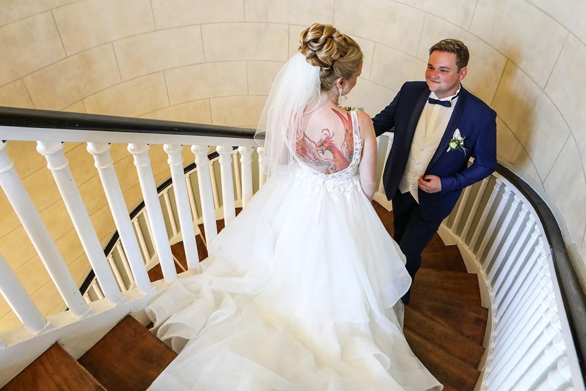 Eine Braut mit einem weißen Brautkleid, langer Schleppe und einem Schleier im Haar geht im Wilhelm-Busch-Mu