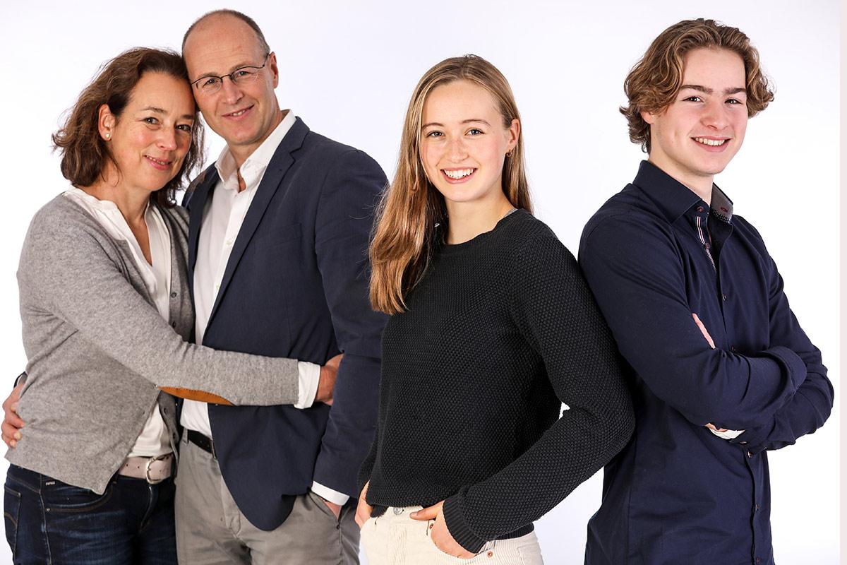 Familienfotos Hannover: Vater und Mutter stehen aneinandergekuschelt links im Hintergrund. Sie blicken auf ihre Mutter und ihren Bruder, die rechts vorn Rücken an Rücken strahlend in die Kamera gucken.