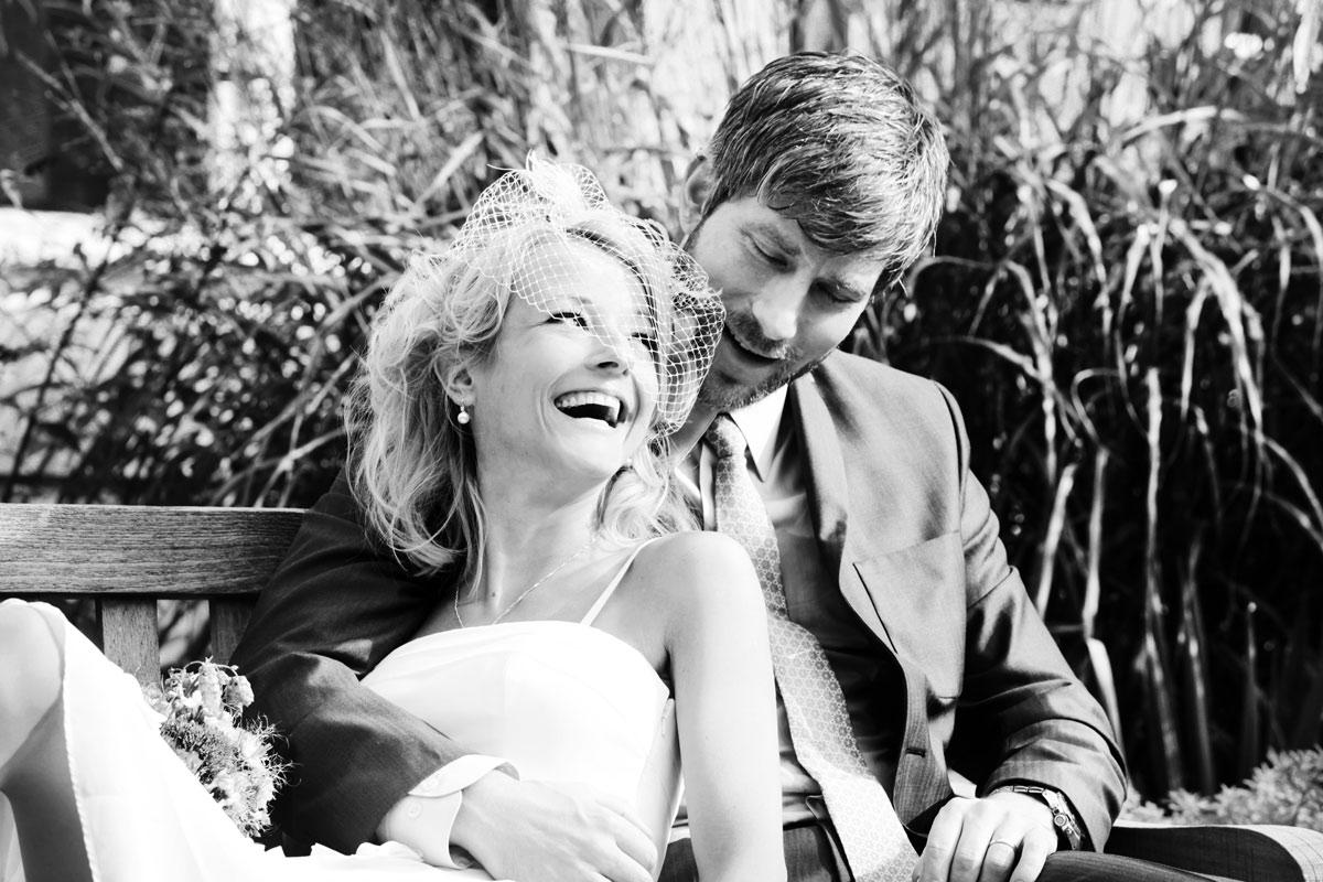 Hochzeitsfotograf Hannover, Brautpaar im Garten des Wilhelm-Busch-Museums lachend auf einer Parkbank