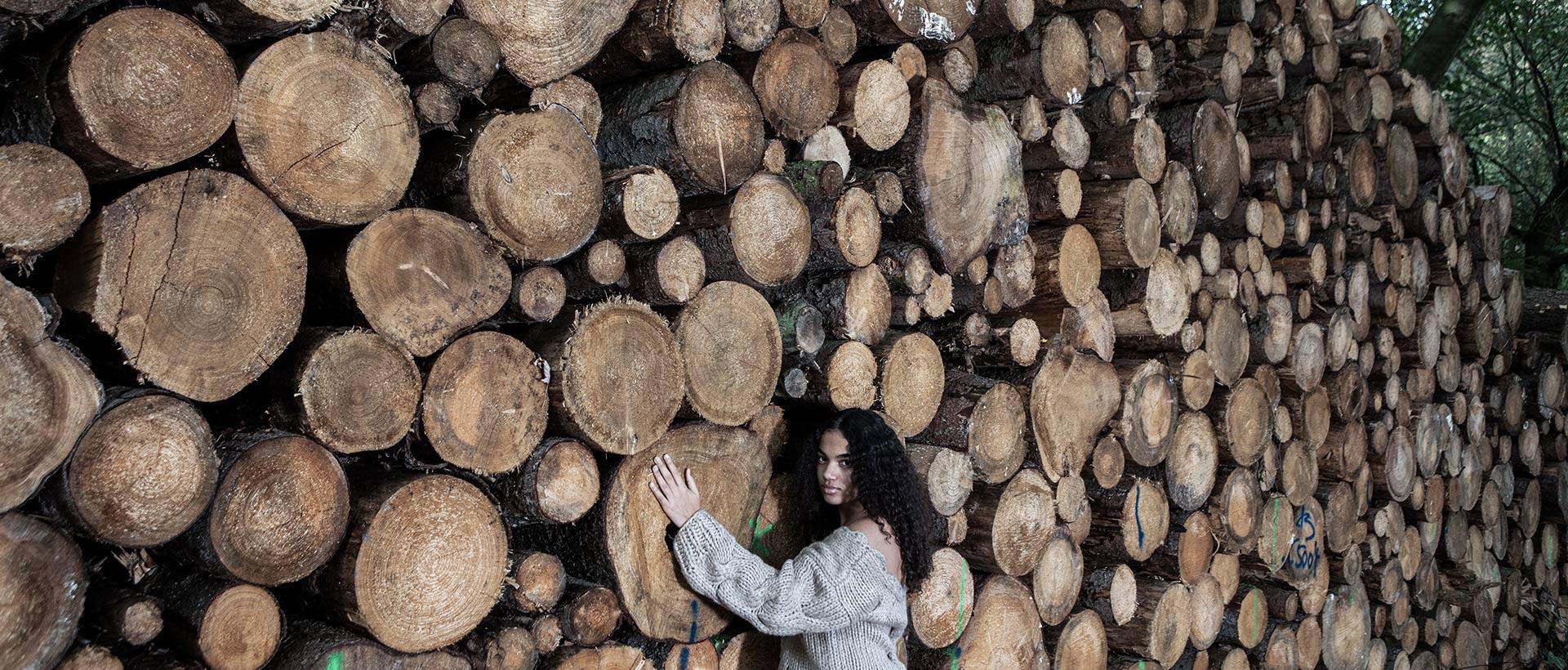 Ein Mädchen lehnt sich an einen Holzstapel, der sie um das Doppelte überragt.